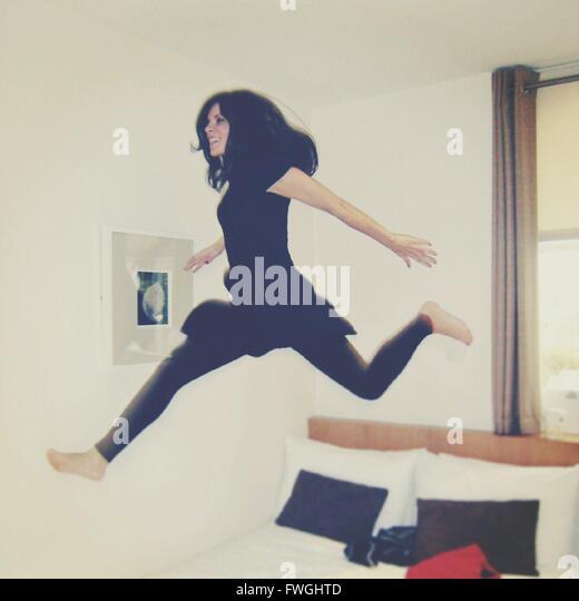 Junge Frau springen auf Bett zu Hause Stockbild