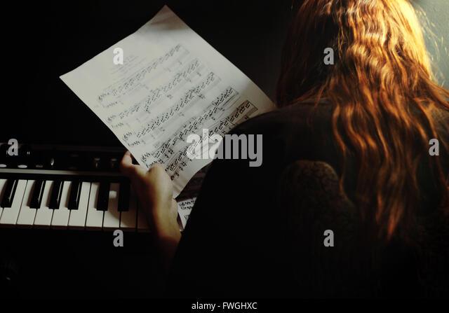 Frau von Musiknoten Klavier Holding Stockbild