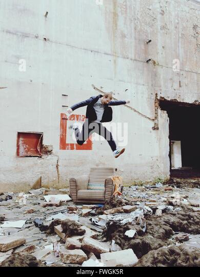 Junger Mann springt über Stuhl außerhalb verlassenen Gebäude Stockbild