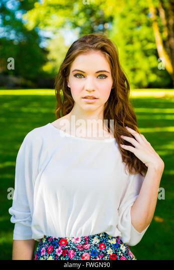 Ein schönes junges Mädchen posiert für ein Mode-Stil-Porträt im Freien in einem Park mit natürlichem Stockbild