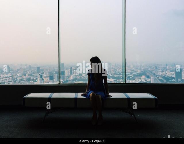 Junge Frau im blauen Kleid sitzt auf Sitz gegen Glasfenster In Stadt Stockbild