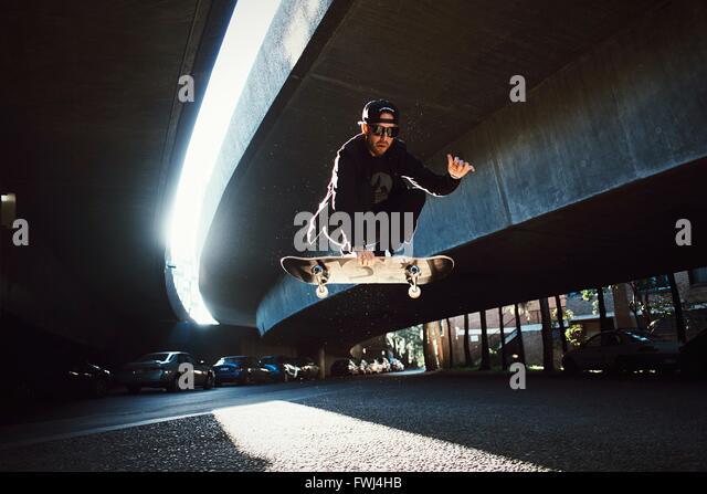 Niedrigen Winkel Ansicht der Mann springt auf Skateboard Stockbild
