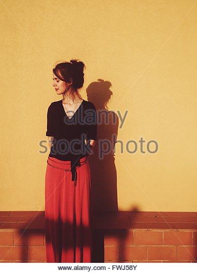 Frau mit geschlossenen Augen stehen gegen die Wand Stockbild