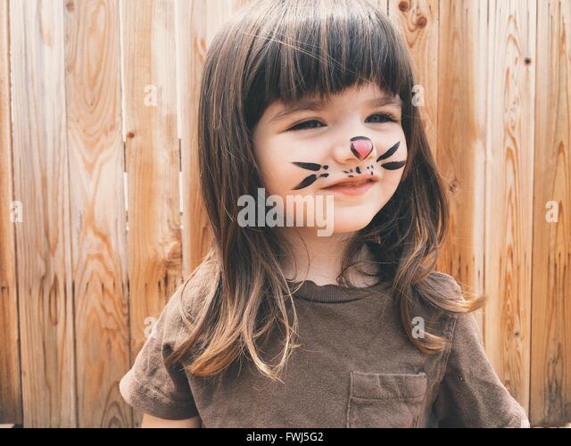Nahaufnahme des Lächelns süßen Mädchens mit Malerei auf Gesicht stehen im freien Stockbild