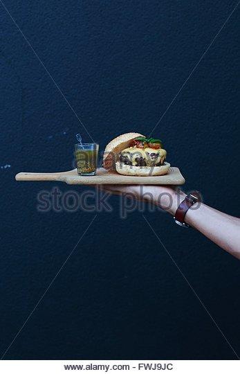 Abgeschnittenen Hand Holding Burger und Getränke auf Schneidebrett gegen Wand Stockbild