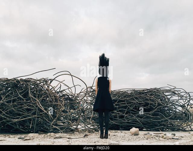 Voller Länge Rückansicht des Frau mit zerzausten Haaren durch verlassene Metall gegen Himmel stehen Stockbild