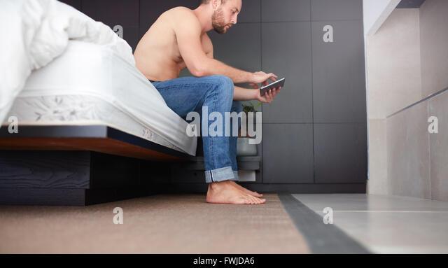 Seite Porträt eines jungen Mannes sitzt auf dem Bett im Schlafzimmer und mit digital-Tablette. Stockbild