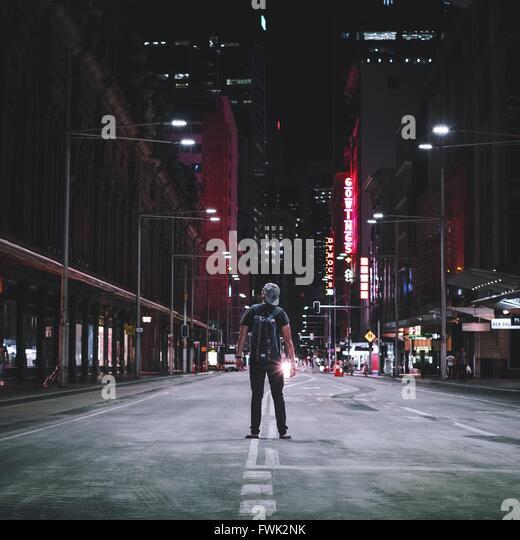 Rückansicht der Mann auf der Straße inmitten von Gebäuden in der Nacht Stockbild