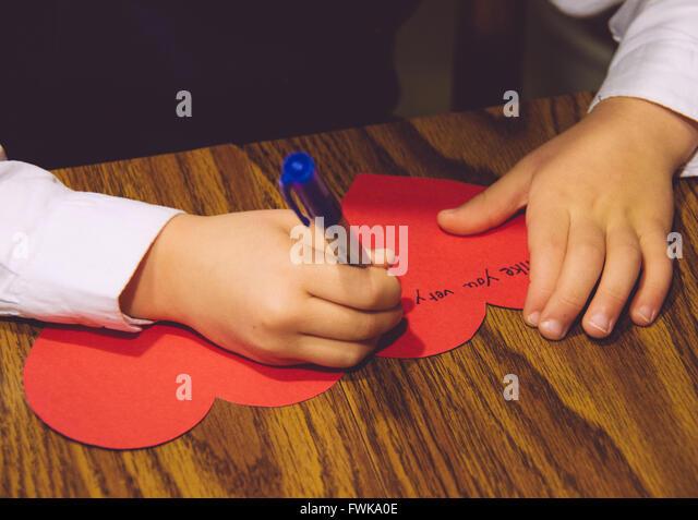 Bild des Kindes Schreibens auf Herz-Form-Grußkarte auf Tabelle abgeschnitten Stockbild