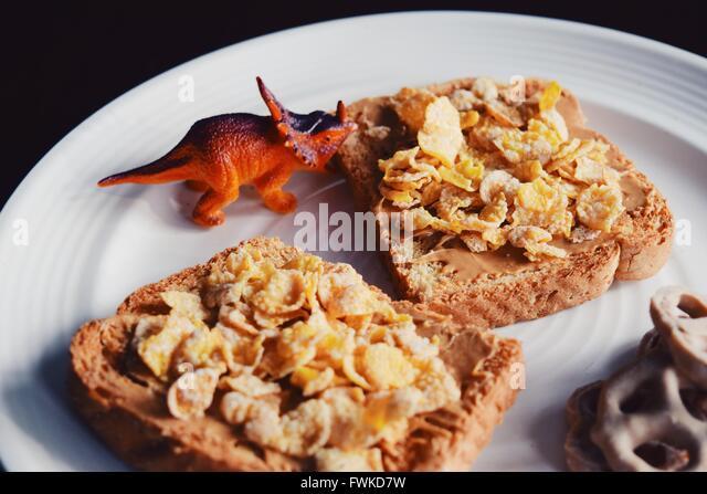 Dinosaurier Spielzeug mit Frühstück auf Platte Stockbild