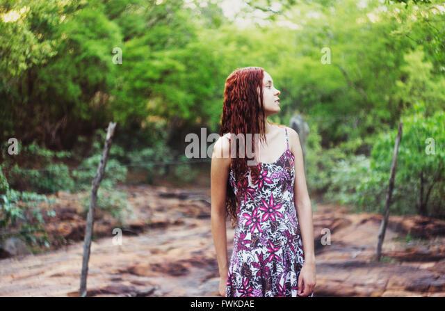 Junge Frau gegen Bäume auf Feld Stockbild