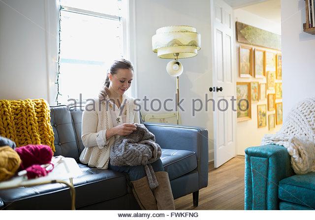 Frau stricken Pullover auf sofa Stockbild