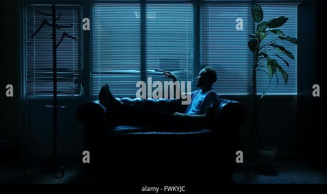 Mann auf Sofa gegen Fenster-Vorhänge Stockbild