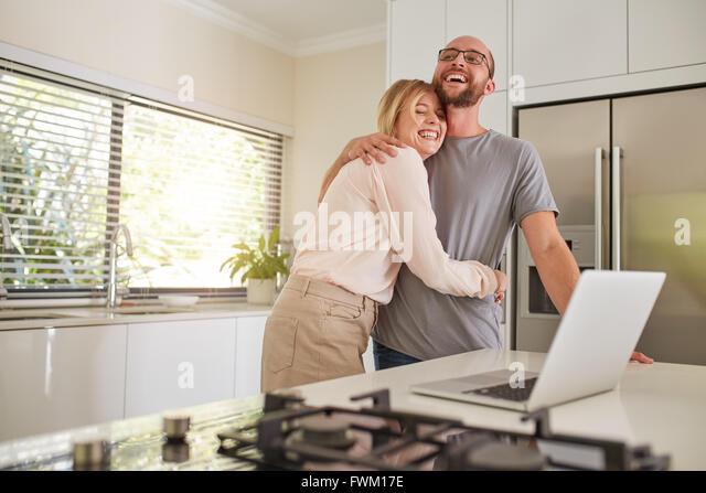 Porträt der glückliche Frau umarmte ihren Mann in der Küche. Liebespaar mit Laptop am Küchentisch Stockbild
