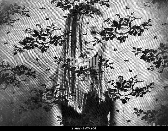 Porträt von Mädchen Gesicht bedeckt mit Haaren gesehen aus Netzstoff Stockbild