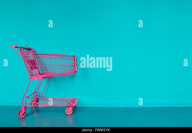 Einkaufswagen gegen türkisfarbenen Wand rosa Stockbild