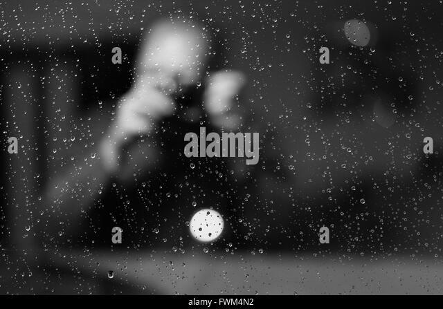 Mann durch nasse Fenster gesehen Stockbild