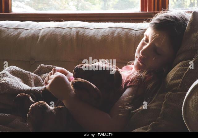 Mädchen mit Teddybär auf Sofa zu Hause schlafen Stockbild
