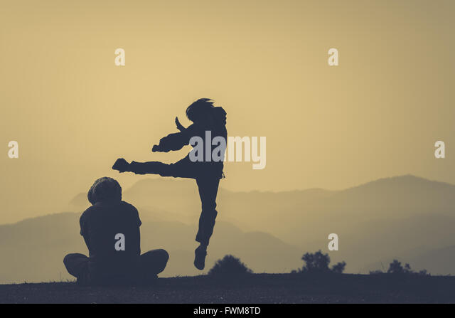 Silhouette-Person, die Ausübung von Freund auf Feld Stockbild