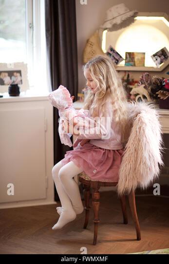 Mädchen spielen mit seiner Babypuppe. Tagespflege, Kind, Spielzimmer, behaupten Spiel. Stockbild