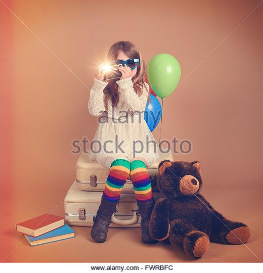 Ein Foto eines Vintage Kindes eine Aufnahme mit einer alten Kamera gegen mit Regenbogen Luftballons und ein Teddybär Stockbild