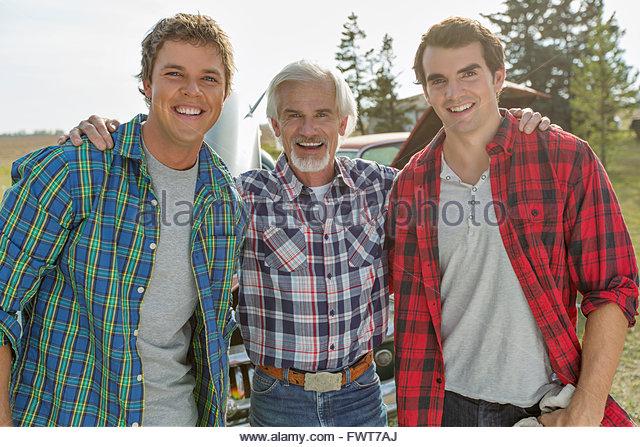 Porträt von Vater und erwachsenen Söhnen in karierten Hemden. Stockbild