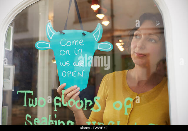 """Weibliche Besitzer des Café drehen Schild """"geöffnet"""" Stockbild"""