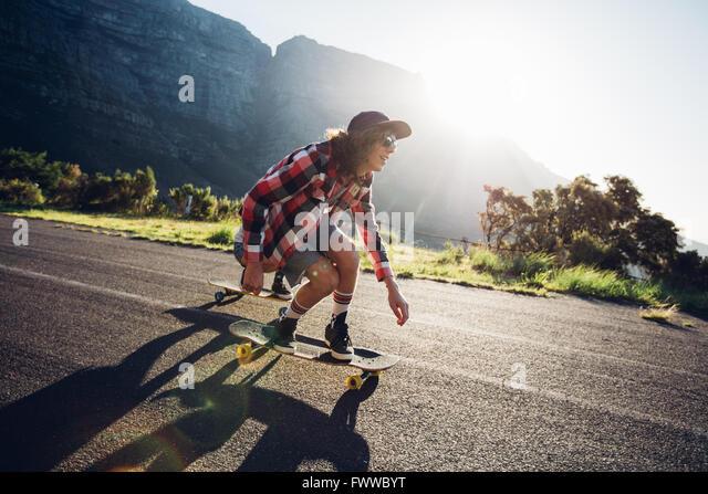Junger Mann Longboarden im freien Landschaft unterwegs. Männlich, skateboarding an einem sonnigen Tag. Stockbild