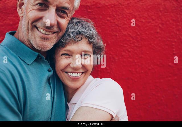 Porträt von fröhlichen mittleren gealterten paar umarmen einander vor rotem Hintergrund. Ältere Mann Stockbild