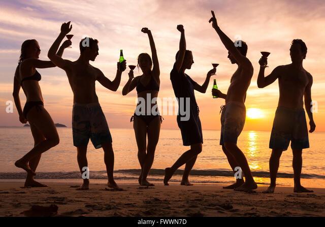 Beach-Party, Gruppe junger Leute, die tanzen, Freunde, trinken Bier und Cocktails bei Sonnenuntergang Stockbild