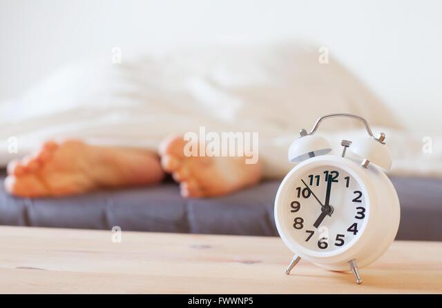 Wecker und Füße der schlafenden Person, morgen Konzept, aufwachen Stockbild