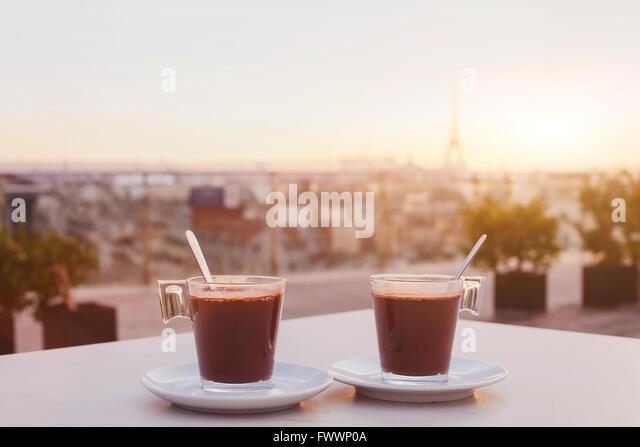 zwei Tassen Kaffee oder heiße Schokolade und Paris Skyline bei Sonnenuntergang, Café mit Panoramablick Stockbild