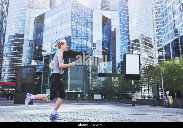 junge Frau läuft auf städtischen Hintergrund Stockbild