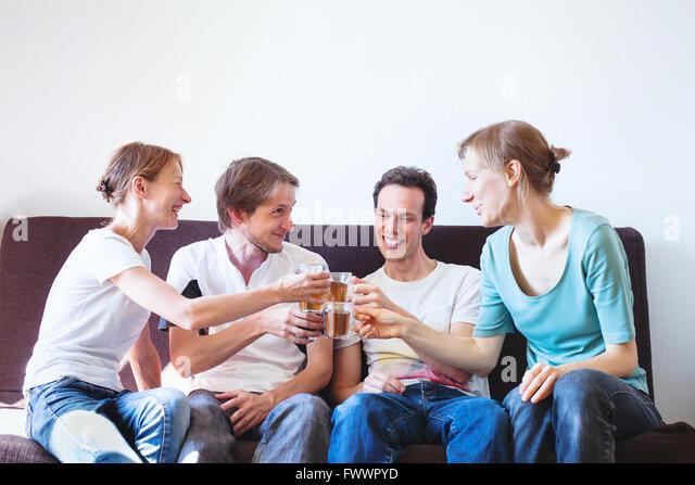 Gruppe von Freunden anfeuern zu Hause glücklich lächelnde Menschen mit Getränken, Exemplar jung Stockbild