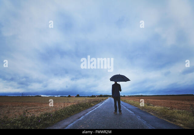 Psychologie-Konzept, Mann mit Regenschirm stehen auf der Straße, Ängste und Einsamkeit Stockbild