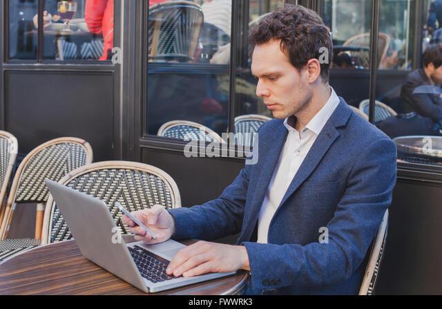 junge hübsche Buisnessman mit Internet auf Handy während der Sitzung in offenen Straßencafé Stockbild