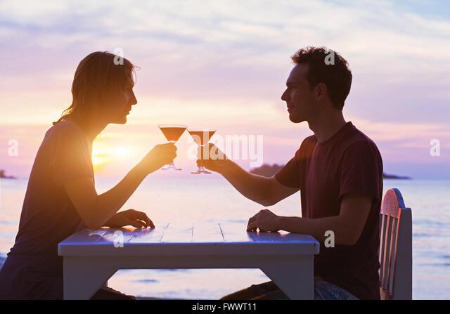 paar im Restaurant, tranken Cocktails am Strand bei Sonnenuntergang Stockbild