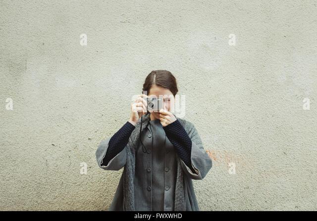 Frankreich, Languedoc-Roussillon, Sauve, junge Touristen mit Kamera gegen Wand - Stock-Bilder