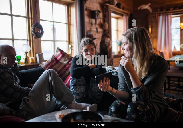 Schweden, junge Frau zeigt Smartphone an Freunde im Blockhaus Stockbild