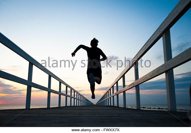 Schweden, Skane, Malmö, junge Frau läuft am Pier bei Sonnenuntergang Stockbild