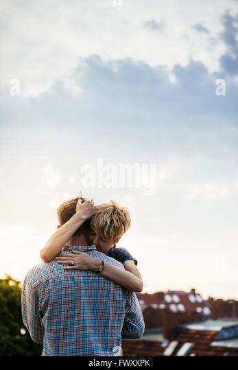 Deutschland, Berlin, junges Paar umarmt auf Dachterrasse bei Sonnenuntergang Stockbild