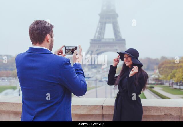 mobile Fotografie, Mann nehmen Foto Frau mit seinem Telefon, paar Touristen nahe dem Eiffelturm in Paris, Frankreich Stockbild