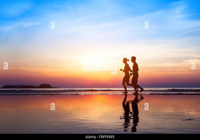 Training-Hintergrund, zwei Menschen, Joggen am Strand bei Sonnenuntergang, Läufer Silhouetten, gesunden Lebensstil Stockbild