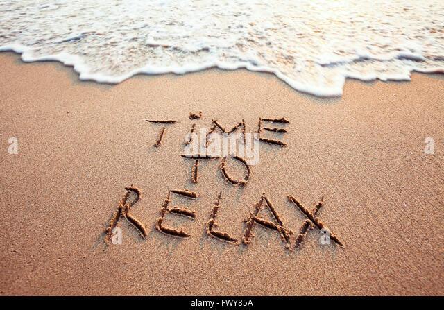 Zeit zum entspannen, Konzept geschrieben am Sandstrand Stockbild