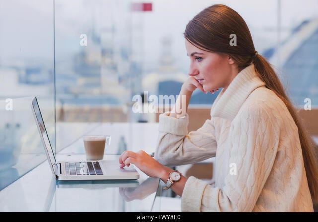 Frau mit Laptop im modernen Café innen, kostenloses Wifi, Abrufen von e-Mails Stockbild