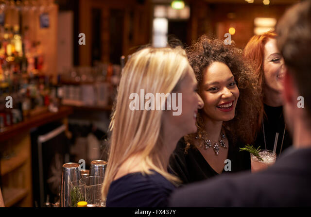 Gruppe von Freunden treffen für Getränke am Abend In der Cocktail-Bar Stockbild