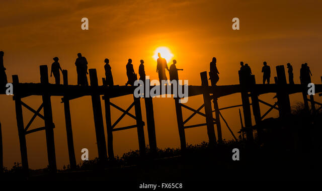 Eine Gruppe von Menschen, die über die hölzerne U-Bein Brücke, Amarapura Township, bei Sonnenuntergang. Stockbild