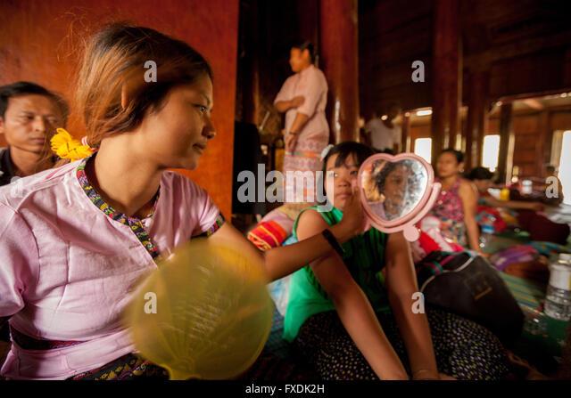Asien, Burma, Myanmar, eine Familie zu Hause im Alltag, eine junge Frau schaut in den Spiegel. Stockbild