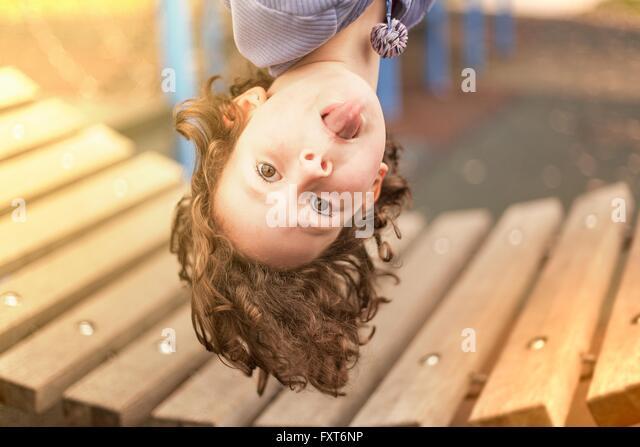 Mädchen im Spielplatz hängen kopfüber Blick in die Kamera, die Zunge - Stock-Bilder