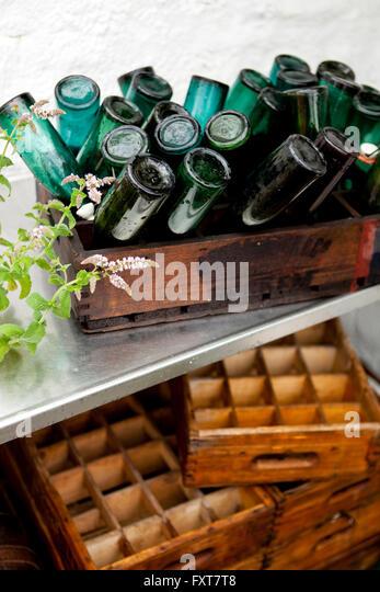 Holzkiste mit Kopf Vintage-Flaschen auf Terrasse im Regen Stockbild